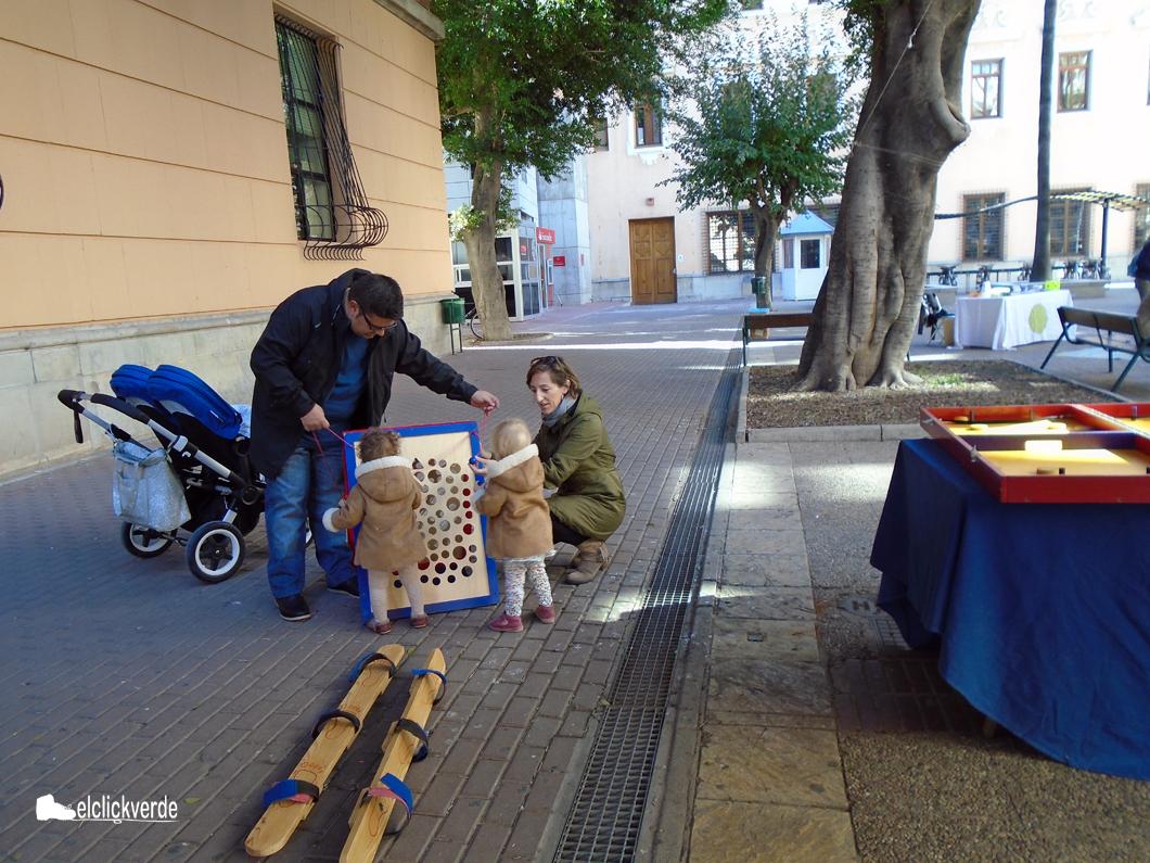 Dos peques, divirtiéndose con sus padres y un juego de madera.
