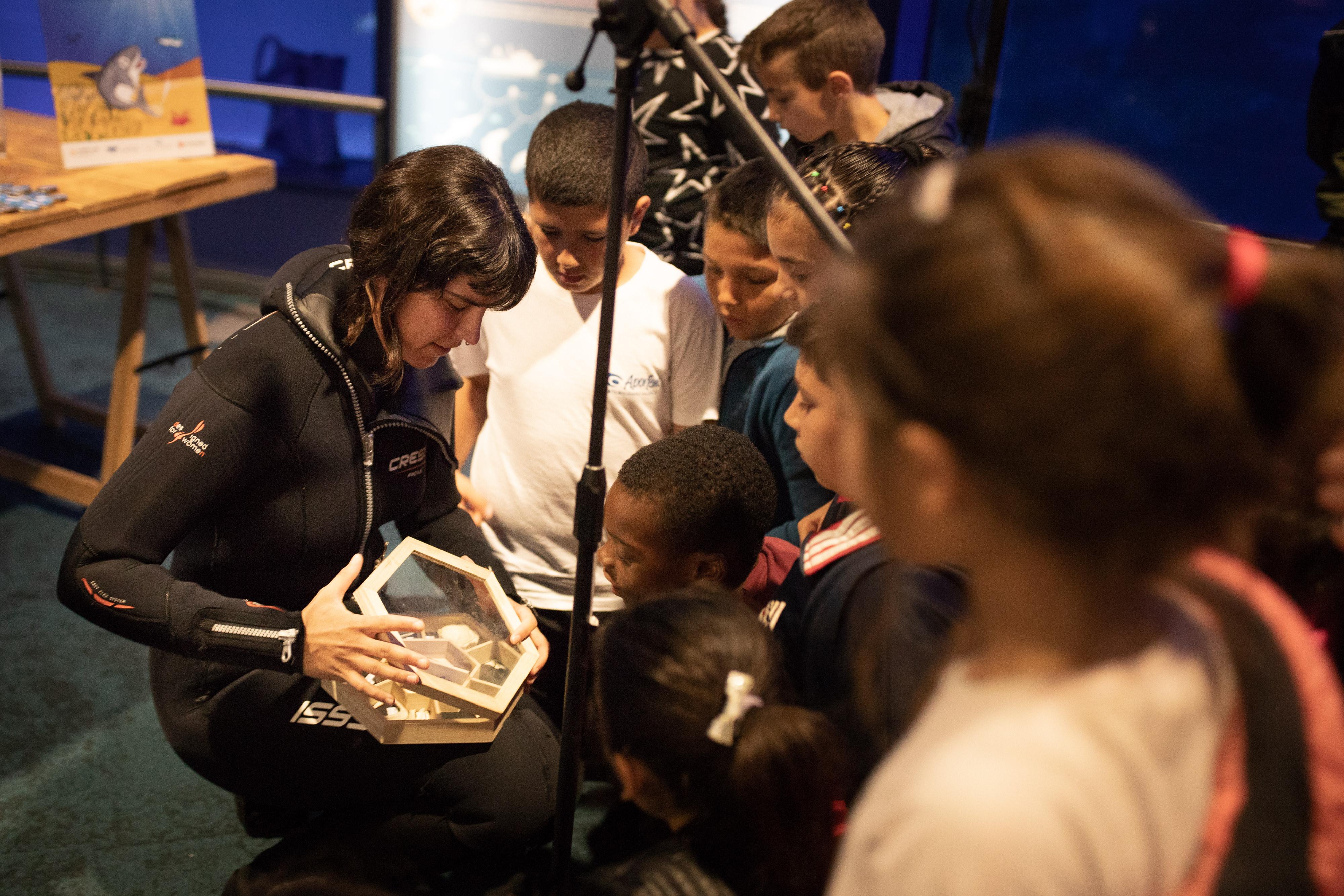 Laura López, del departamento de Océanos, enseña muestras biológicas a los niños asistentes. Imagen: Oceanogràfic