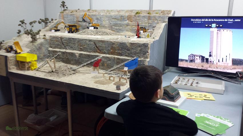 Un niño observa el vídeo de una demolición al lado de la reproducción de una mina elaborada por la UPCT y bien explicada por sus científicos, anoche en la Semana de la Ciencia y la Tecnología de la Región de Murcia.