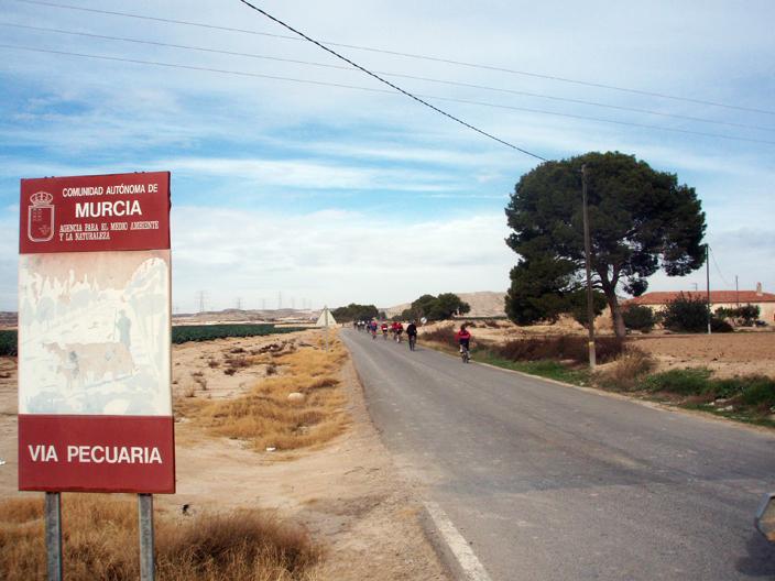 El grupo ciclista cruza el cartel anunciador de la Vereda Real. Imagen: Murciaenbici